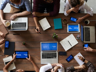top view photo of people near wooden table with laptops