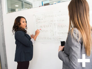 two women conversing in front of a whiteboard