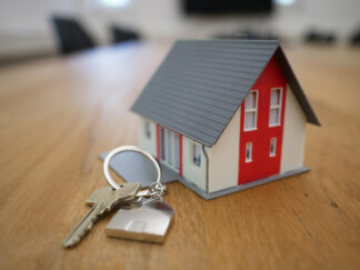 photo of a wooden house model and keys