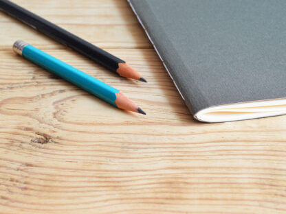 two pencils next to a notebook