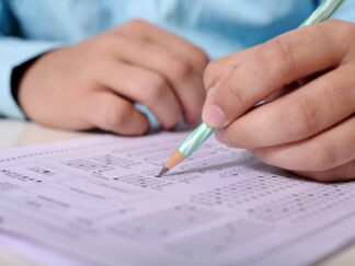 man filling out exam answer sheet
